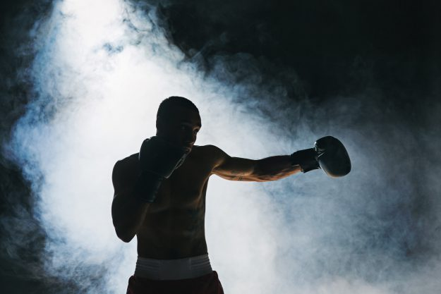 HOw to make the break out: Afro american male boxer. Young man boxing workout in a fitness club. Muscular strong man on background black studio